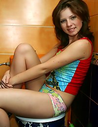 Petite teen Kimmy in a bathroom stall posing on a toilet!